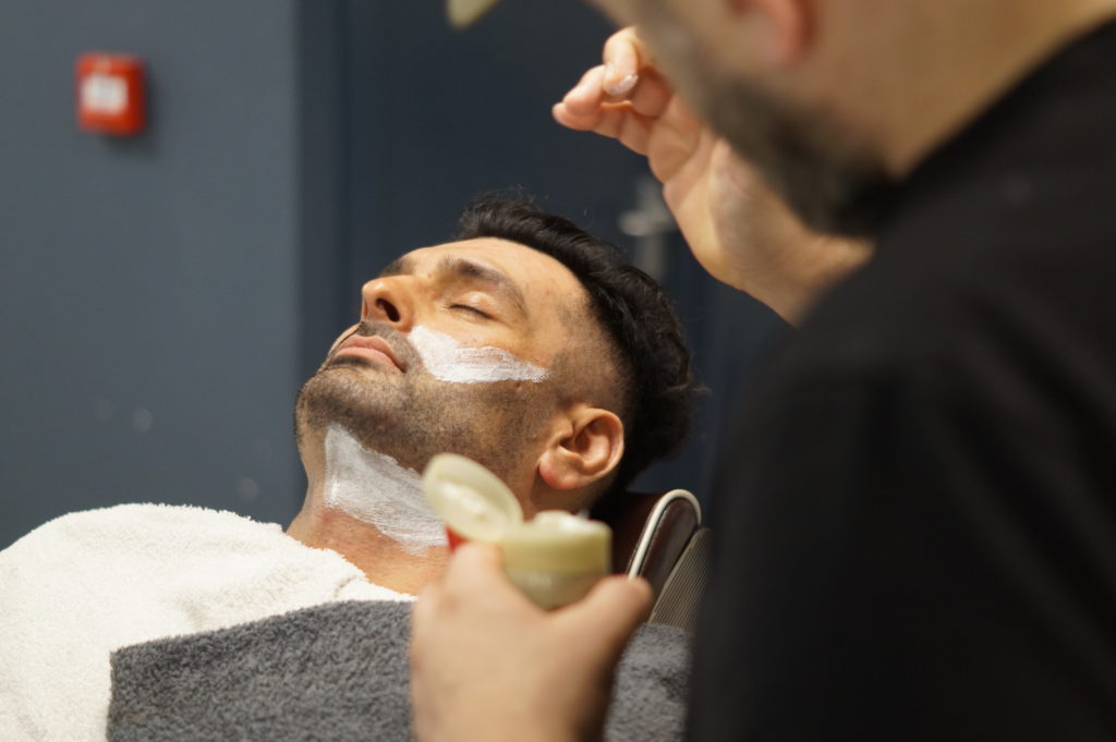 Deluxe Clinique & Lab Series Facial; a barber performing a facial to a client