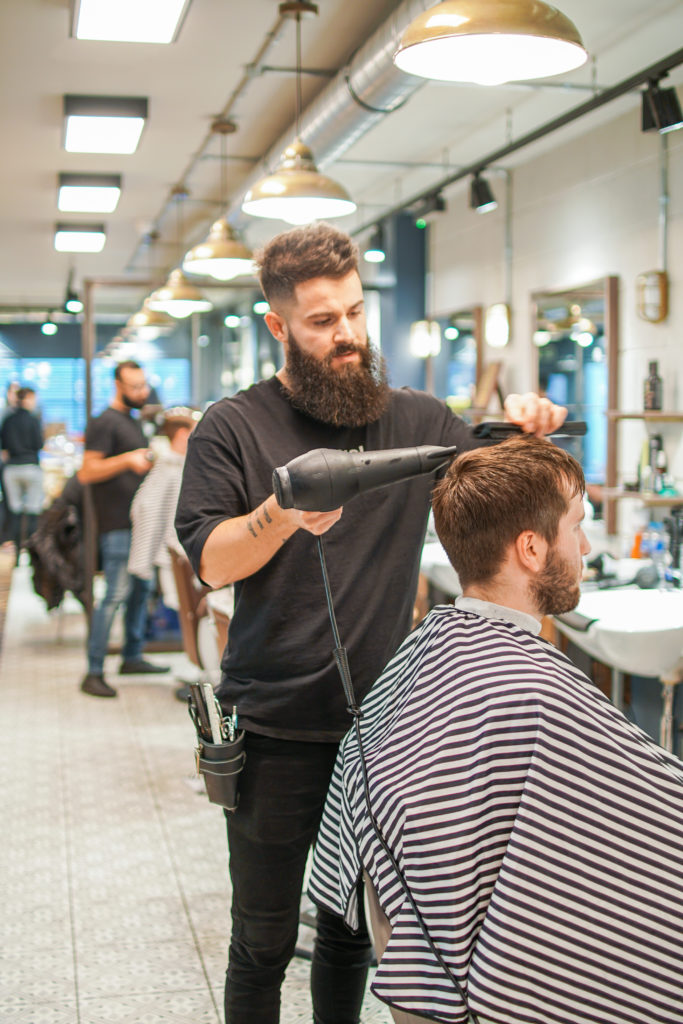 shampoo & style barbers se1; a barber blow drying the client